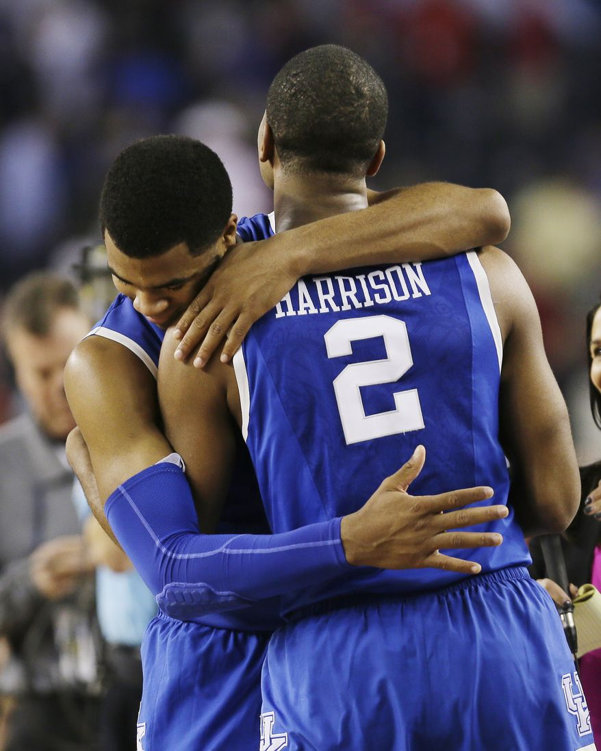 After Kentucky guard Aaron Harrison (2) made a three-point basket in the final seconds against Wisconsin to win the game 74-73, he is embraced guard Andrew Harrison after their NCAA Final Four tournament college basketball semifinal game Saturday, April 5, 2014, in Arlington, Texas. (AP Photo/Charlie Neibergall)