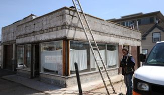 In this photo taken on April 17, 2014, Jim Mannor works on the building of a planned year-round farmer's market at 325 W. Liberty, the site of a former gas station and medical marijuana dispensary, in Ann Arbor, Mich. (AP Photo/The Ann Arbor News, Brianne Bowen) LOCAL TV OUT; LOCAL INTERNET OUT