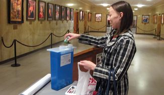 Amy Schutt deposits unwanted  prescription drugs at a special receptacle at the state Capitol in Bismarck, N.D. on Friday, April 25, 2014. Attorney General Wayne Stenehjem says the state program that collects unused medication to help fight prescription drug abuse has destroyed 3.3 tons of OxyContin and other drugs in the past five years. (AP Photo/James MacPherson)
