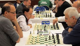 In this photo taken on Thursday, April 24, 2014, chess players consider their next move as the compete in the 41st United Nations Inter-Agency Games at Hofstra University in Hempstead, N.Y. The games were started in the early 1970s, but this is the first time the athletes are competing in the United States; all previous games have been in Europe. (AP Photo/Frank Eltman)