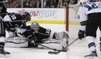 Los Angeles Kings goalie Jonathan Quick, middle, blocks a shot by San Jose Sharks center Patrick Marleau, right, as Mike Richards looks during the third period in Game 4 of an NHL hockey first-round playoff series in Los Angeles, Thursday, April 24, 2014. (AP Photo/Chris Carlson)