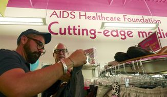 In a Saturday April 19, 2014 photo, Alfonso Serrano, left, and Mark Carrigan shop during the grand opening at the Out of the Closet Thrift Store in Dallas. The stores are part of the AIDS Healthcare Foundation and 96 cents of every dollar earned  goes into supporting AHF clinics serving nearly 300,000 people worldwide. (AP Photo/The Dallas Morning News, Ron Baselice)