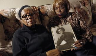 FILE- In this March 12, 2014 file photo, Alma Murdough and her daughter Cheryl Warner hold a photo of Murdough's son, at her home in the Queens borough of New York.  Jerome Murdough, a mentally ill, homeless former Marine arrested for sleeping in the roof landing of a New York City public housing project during one of the coldest recorded winters in city history, died in a Rikers Island jail cell that multiple city officials say was at least 100 degrees when his body was discovered. The former Marine will be buried in New Jersey on Friday, April 25, 2014, after a modest funeral service in the Queens borough of New York. (AP Photo/Jason DeCrow, File)
