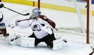 A shot by Minnesota Wild defenseman Jared Spurgeon gets past Colorado Avalanche goalie Semyon Varlamov (1), of Russia, for a goal during the first period of Game 4 of an NHL hockey first-round playoff series in St. Paul, Minn., Thursday, April 24, 2014. (AP Photo/Ann Heisenfelt)