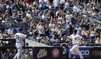 New York Yankees' John Ryan Murphy runs home, as third base coach Rob Thomson waits to greet him, after hitting a solo home run in the fifth inning of a baseball game against the Los Angeles Angels at Yankee Stadium, Saturday, April 26, 2014, in New York. (AP Photo/John Minchillo)