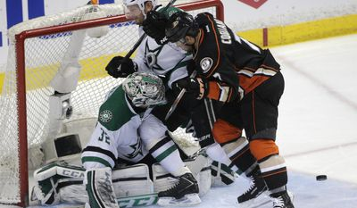 Anaheim Ducks' Andrew Cogliano, right, pushes Dallas Stars' Sergei Gonchar, center, in front of Stars goalie Kari Lehtonen, of Finland, during the second period of Game 5 of the first-round NHL hockey Stanley Cup playoff series on Friday, April 25, 2014, in Anaheim, Calif. (AP Photo/Jae C. Hong)