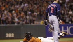 San Francisco Giants' Pablo Sandoval, bottom, slides safely into third base with a triple next to Cleveland Indians third baseman Lonnie Chisenhall (8) during the seventh inning of a baseball game on Friday, April 25, 2014, in San Francisco. (AP Photo/Marcio Jose Sanchez)