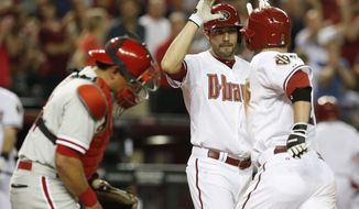 Arizona Diamondbacks' Aaron Hill, right, gets a high-five from teammate A.J. Pollock, second from right, after Hill hit a 2-run home run, as Philadelphia Phillies' Carlos Ruiz, left, looks away during the fourth inning of a baseball game on Friday, April 25, 2014, in Phoenix. (AP Photo/Ross D. Franklin)