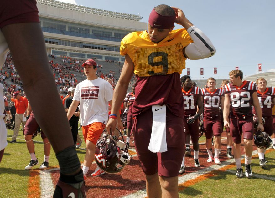Virginia Tech quarterback Brenden Motley, front, walks off the field with his teammates after the annual Maroon-White NCAA college spring football game in Blacksburg, Va., Saturday, April 26, 2014. (AP Photo/The Roanoke Times, Matt Gentry)