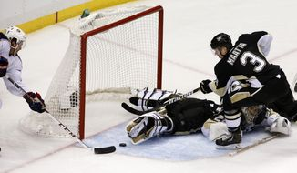 Columbus Blue Jackets' Boone Jenner, left, prepares to put the puck into the net for a goal behind Pittsburgh Penguins goalie Marc-Andre Fleury and Olli Maatta (3) in the first period of Game 5 of a first-round NHL playoff hockey series in Pittsburgh, Saturday, April 26, 2014. (AP Photo/Gene J. Puskar)