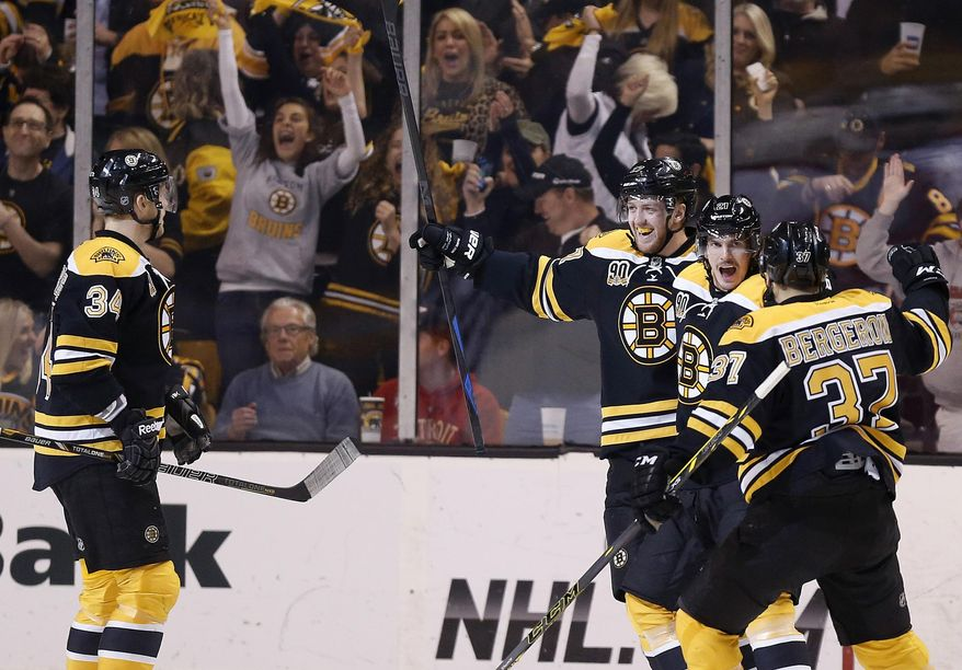Boston Bruins' Loui Eriksson, second from right, celebrates his goal with teammates during the first period  in Game 5 in the first round of the NHL hockey Stanley Cup playoffs against the Detroit Red Wings in Boston, Saturday, April 26, 2014. (AP Photo/Michael Dwyer)