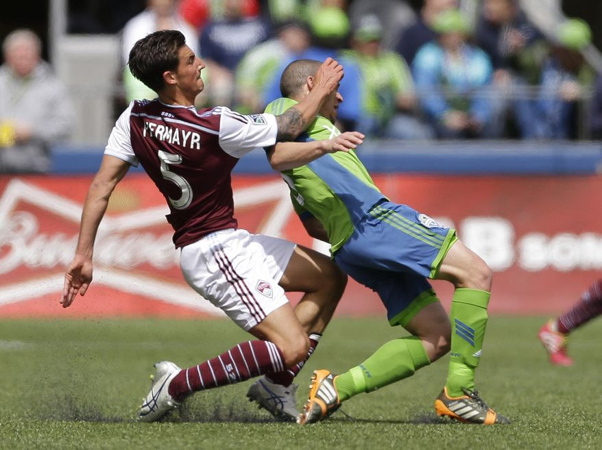 Seattle Sounders' Osvaldo Alonso, right is fouled by Colorado Rapids' Thomas Piermayr, left, Saturday, April 26, 2014, in the first half of an MLS soccer match in Seattle. Piermayr was given a yellow card on the play. (AP Photo/Ted S. Warren)