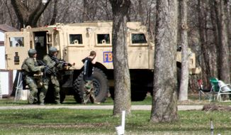 "FILE - This May 3, 2013, photo provided by Jeremy Jones shows authorities with Buford Rogers, right,  who belongs to a tiny local militia, during a raid on a mobile home in Montevideo, Minn. Rogers, 25, is scheduled to be sentenced Monday, April 28, 2011 after pleading guilty to one count of possessing a firearm illegally and one count of possessing an unregistered destructive device, namely ""two black powder and nail devices,"" which he admitted he made himself. Prosecutors are seeking more than five years in prison, arguing that Rogers poses a threat to public safety, noting the items were designed solely to injure people. (AP Photo/Montevideo American-News, Jeremy Jones, File) MANDATORY CREDIT"