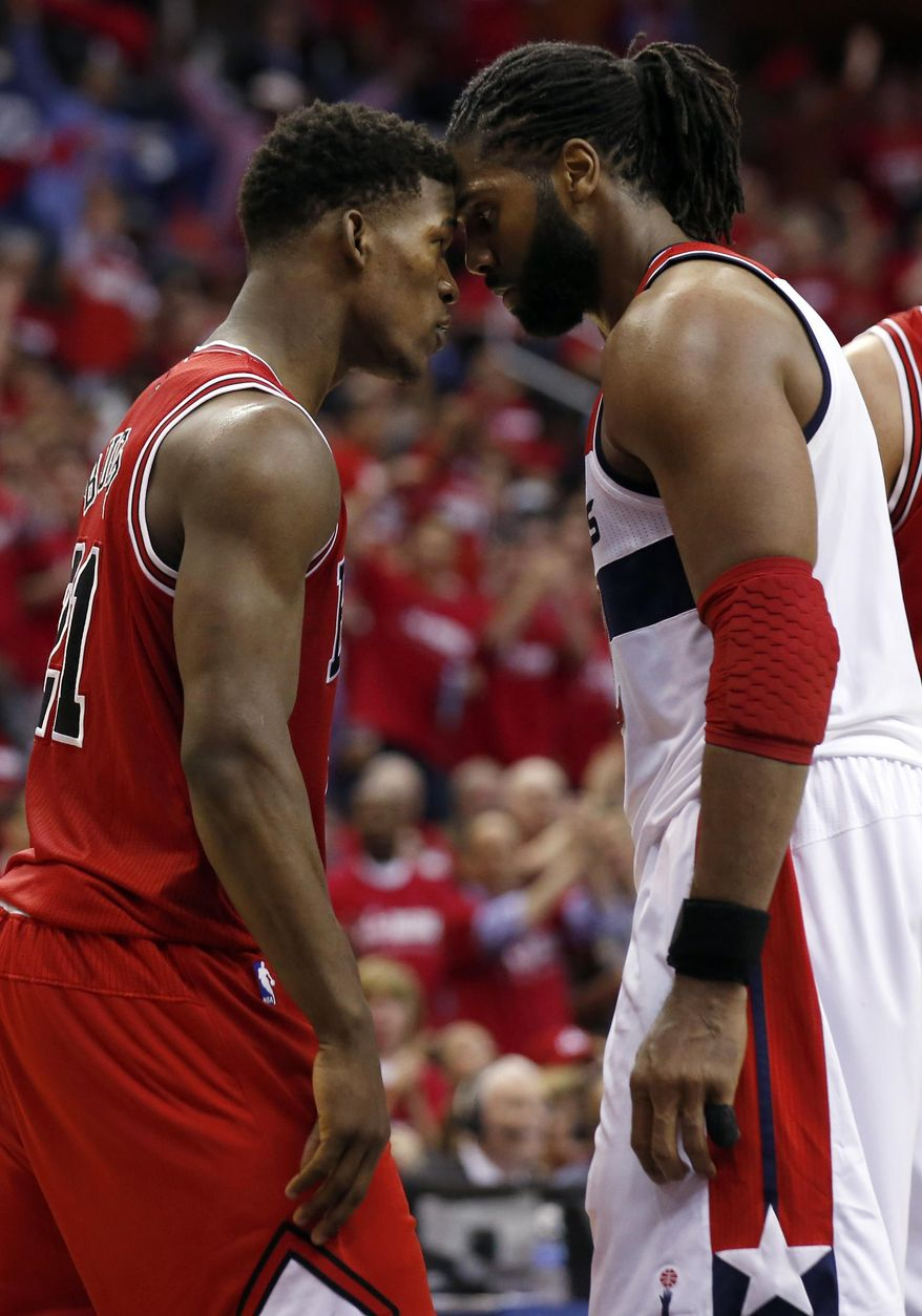 Chicago Bulls guard Jimmy Butler (21) and Washington Wizards forward Nene (42), from Brazil, stand head-to-head in the second half of Game 3 of an opening-round NBA basketball playoff series on Friday, April 25, 2014, in Washington. Nene received a double technical and was ejected. The Bulls won 100-97. (AP Photo/Alex Brandon)