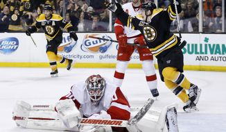 Detroit Red Wings' Jonas Gustavsson (50) sprawls on the ice as Boston Bruins' Torey Krug, center, celebrates a goal by teammate Zdeno Chara during the second period in Game 5 in the first round of the NHL hockey Stanley Cup playoffs  in Boston, Saturday, April 26, 2014. (AP Photo/Michael Dwyer)