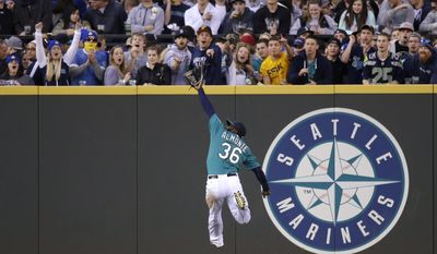 Seattle Mariners center fielder Abraham Almonte leaps for but misses an RBI-double by Texas Rangers' Adrian Beltre in the fourth inning of a baseball game on Friday, April 25, 2014, in Seattle. (AP Photo/Elaine Thompson)