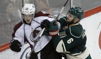 Minnesota Wild defenseman Marco Scandella (6) shoves Colorado Avalanche center Nathan MacKinnon (29) into the boards during the third period of Game 4 of an NHL hockey first-round playoff series in St. Paul, Minn., Thursday, April 24, 2014. The Wild won 2-1. (AP Photo/Ann Heisenfelt)