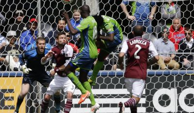 Seattle Sounders' Obafemi Martins, second from right, and Djimi Traore (18) try to head the ball as Colorado Rapids goalkeeper Clint Irwin, left, and defender Drew Moor (3) look on, Saturday, April 26, 2014, in the first half of an MLS soccer match in Seattle. (AP Photo/Ted S. Warren)