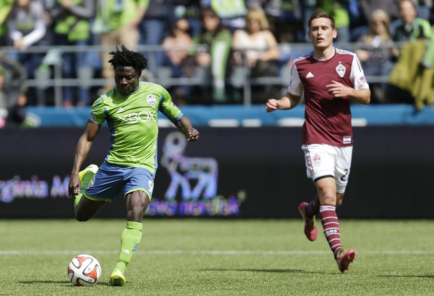 Seattle Sounders' Obafemi Martins, left, kicks a goal as Colorado Rapids defender Shane O'Neill looks on at right, Saturday, April 26, 2014 in the second half of an MLS soccer match in Seattle. The Sounders defeated the Rapids 4-1. (AP Photo/Ted S. Warren)