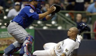 Milwaukee Brewers' Carlos Gomez, right, scores ahead of the tag by Chicago Cubs catcher Welington Castillo during the first inning of a baseball game on Saturday, April 26, 2014, in Milwaukee. Gomez scored a sacrifice fly hit by Aramis Ramirez. (AP Photo/Jeffrey Phelps)