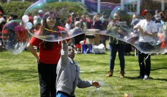 Children play with huge bubbles during the Rutgers Day events  in New Brunswick, N.J., Saturday, April 26, 2014. The annual event showcases hundreds of events and programs sponsored by schools, departments, institutes, centers and student organizations on the university's campuses in New Brunswick and Piscataway. (AP Photo/Mel Evans)
