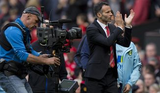 Manchester United's interim manager Ryan Giggs applauds supporters after his team's 4-0 win against Norwich City in their English Premier League soccer match at Old Trafford Stadium, Manchester, England, Saturday April 26, 2014. (AP Photo/Jon Super)