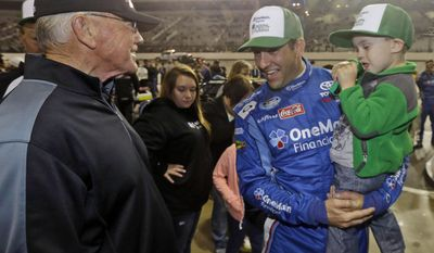 Team owner Joe Gibbs, left, talks with driver Elliot Sadler as he holds his son, Wyatt, 4, prior to the start of the NASCAR Nationwide series auto race at the Richmond International Raceway in Richmond, Va., Friday, April 25, 2014.   (AP Photo/Steve Helber)
