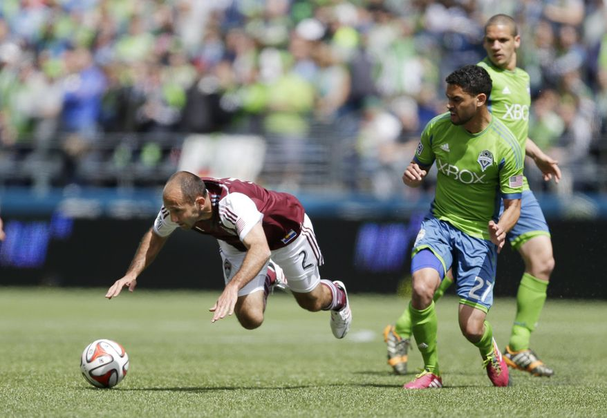 Colorado Rapids' Nick LaBrocca (2) goes down on a play involving Seattle Sounders' Lamar Neagle, second from right, Saturday, April 26, 2014, in the first half of an MLS soccer match in Seattle. (AP Photo/Ted S. Warren)