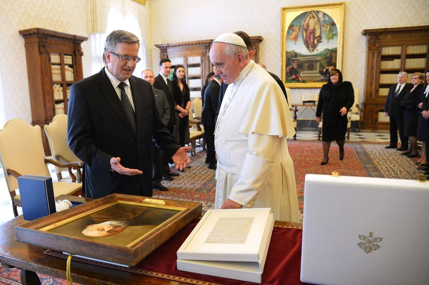 Polish President Bronislaw Komorowski, left, and Pope Francis exchange gifts on the occasion of their private audience at the Vatican, Saturday, April 26, 2014. Komorowski is in Rome to attend Sunday's canonization ceremony for John Paul II and John XXIII where Pope Francis will elevate the two popes to sainthood.(AP Photo/Vincenzo Pinto, Pool)