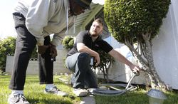 In this photo taken Tuesday, March 11, 2014, Steve Upton, right, explains to Larry Barber how to use the water timer Upton installed on the water spigot at the Barber home in Sacramento, Calif.  Upton, an inspector for the water conservation unit of the Sacramento Utilities department, follows up on tips concerning city residents wasting water in one of California's driest years on record.  During his visit to the Barbers, after receiving a tip they were watering their lawn on a non-watering day, Upton installed the water timer and gave them information on how to conserve water.(AP Photo/Rich Pedroncelli)