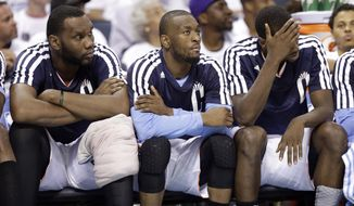 Charlotte Bobcats players, from left, Al Jefferson, Kemba Walker, and Michael Kidd-Gilchrist watch from the bench during the second half in Game 3 of an opening-round NBA basketball playoff series against the Miami Heat in Charlotte, N.C., Saturday, April 26, 2014. The Heat won 98-85. (AP Photo/Chuck Burton)
