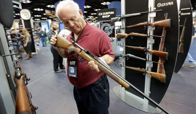 Jerry Miller of Georgetown, Texas, looks over a rifle at the NRA convention, where members were setting their sights on elections and reining in gun control legislation. (Associated Press Photographs)