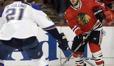 Chicago Blackhawks' Brent Seabrook, right, looks to a pass against St. Louis Blues' Patrik Berglund (21) during the first period in Game 6 of a first-round NHL hockey playoff series in Chicago, Sunday, April 27, 2014. (AP Photo/Nam Y. Huh)