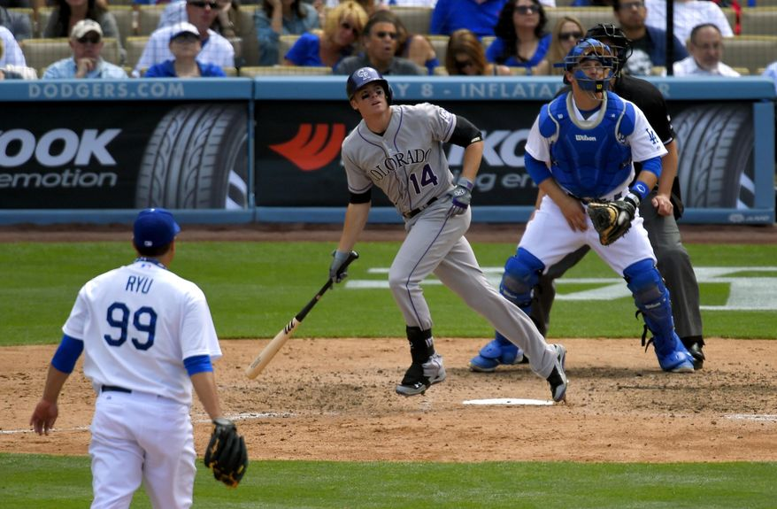 Colorado Rockies' Josh Rutledge, center, hits a three-run home run as Los Angeles Dodgers starting pitcher Ryu Hyun-Jin, left, of South Korea, and catcher Tim Federowicz look on during the sixth inning of a baseball game, Sunday, April 27, 2014, in Los Angeles. (AP Photo/Mark J. Terrill)