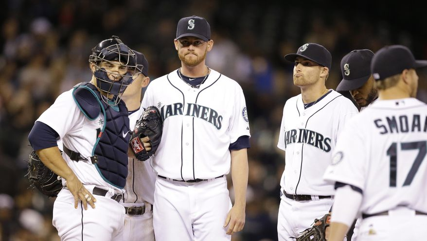 Seattle Mariners relief pitcher Charlie Furbush, second left, waits to be relieved after throwing a total of three pitches against the Texas Rangers in the eighth inning of a baseball game Saturday, April 26, 2014, in Seattle. The Rangers won 6-3. (AP Photo/Elaine Thompson)