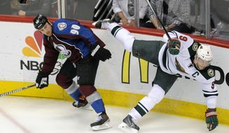 Colorado Avalanche center Ryan O'Reilly, left, and Minnesota Wild center Mikko Koivu, of Finland, right, collide in overtime in Game 5 of an NHL hockey first-round playoff series on Saturday, April 26, 2014, in Denver. The Avalanche won 4-3. (AP Photo/Chris Schneider)