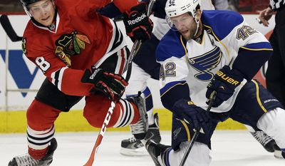Chicago Blackhawks' Ben Smith, left, and St. Louis Blues' David Backes battle for the puck during the first period in Game 6 of a first-round NHL hockey playoff series in Chicago, Sunday, April 27, 2014. (AP Photo/Nam Y. Huh)