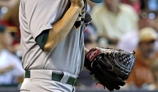 Oakland Athletics starting pitcher Tommy Milone wipes his face after giving up a single to Houston Astros' Jose Altuve in the third inning of a baseball game on Sunday, April 27, 2014, in Houston. (AP Photo/Pat Sullivan)
