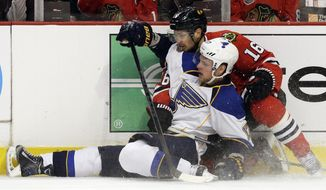 St. Louis Blues' Vladimir Sobotka (17) is checked by Chicago Blackhawks' Marcus Kruger (16) during the first period in Game 6 of a first-round NHL hockey playoff series in Chicago, Sunday, April 27, 2014. (AP Photo/Nam Y. Huh)