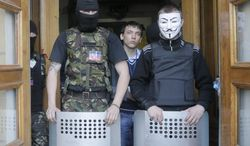 Masked pro-Russian activists guard the entrance during their mass storming of a regional Television Centre in Donetsk, Ukraine, Sunday, April 27, 2014.  Insurgents in Slovyansk have taken a number of people hostage, including journalists and pro-Ukraine activists, as they strengthen their control in the east of the country in defiance of the interim government in Kiev and its Western supporters. (AP Photo/Efrem Lukatsky)