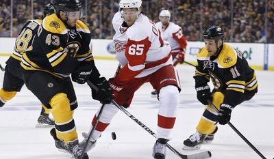 Boston Bruins' Matt Bartkowski (43) and Detroit Red Wings' Danny DeKeyser (65) battle for the puck during the first period in Game 5 in the first round of the NHL hockey Stanley Cup playoffs  in Boston, Saturday, April 26, 2014. (AP Photo/Michael Dwyer)