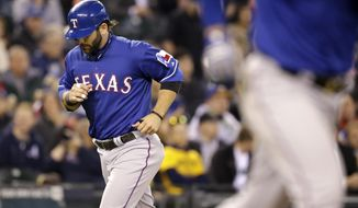 Texas Rangers' Mitch Moreland scores on a bases-loaded walk to Robinson Chirinos by the Seattle Mariners in the fifth inning of a baseball game on Saturday, April 26, 2014, in Seattle. (AP Photo/Elaine Thompson)