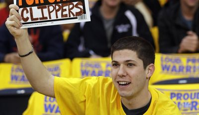 Fan Kevin Phillips holds up a sign making light of controversies surrounding the Los Angeles Clippers before Game 4 of an opening-round NBA basketball playoff series against the Golden State Warriors on Sunday, April 27, 2014, in Oakland, Calif. (AP Photo/Marcio Jose Sanchez)