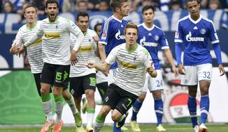 Moenchengladbach's Patrick Herrmann, center, celebrates after scoring the opening goal during  the German Bundesliga soccer match between FC Schalke 04 and Borussia Moenchengladbach in Gelsenkirchen,  Germany, Sunday, April 27, 2014. (AP Photo/Martin Meissner)