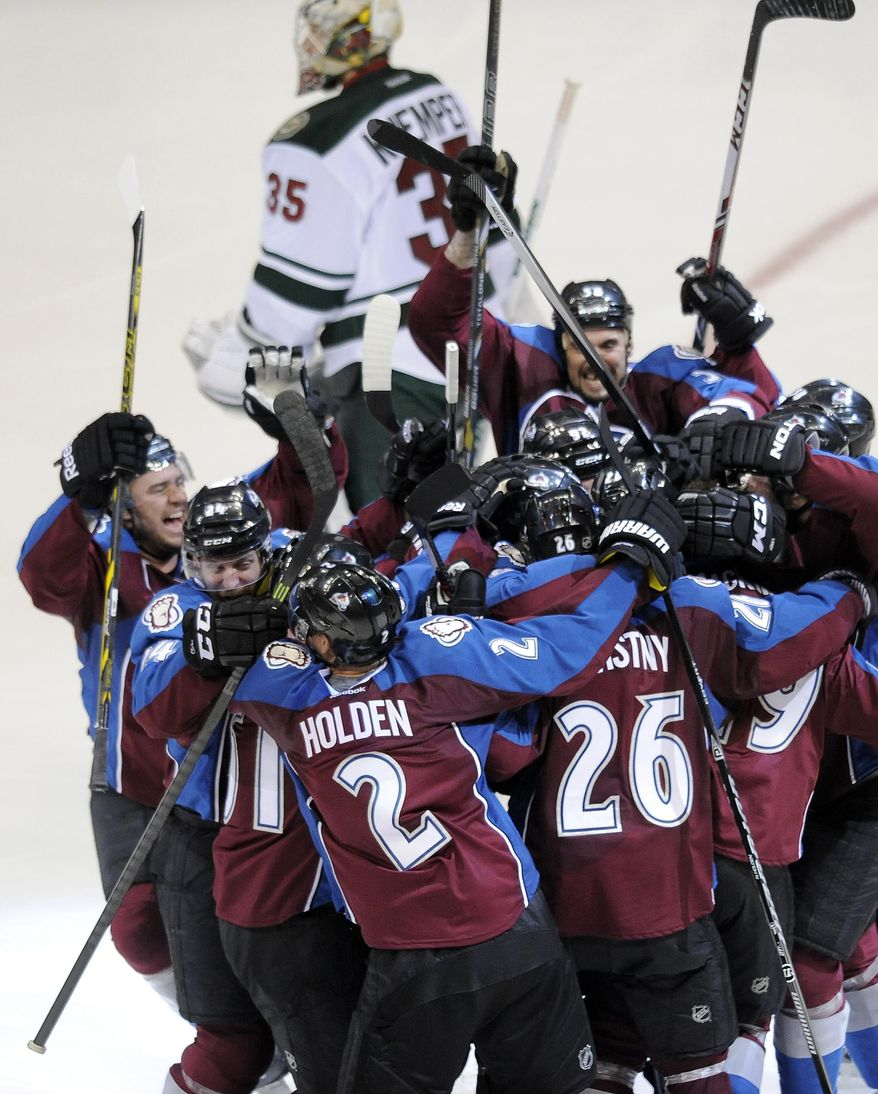 The Colorado Avalanche celebrate as Minnesota Wild goalie Darcy Kuemper skates past after a game-winning goal by Nathan MacKinnon in overtime in Game 5 of an NHL hockey first-round playoff series on Saturday, April 26, 2014, in Denver. The Avalanche won 4-3. (AP Photo/Chris Schneider)