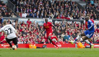 Chelsea's Demba Ba, right, scores against Liverpool during their English Premier League soccer match at Anfield Stadium, Liverpool, England, Sunday April 27, 2014. (AP Photo/Jon Super)