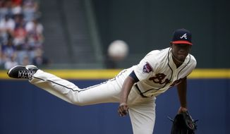 Atlanta Braves starting pitcher Julio Teheran throws in the first inning of a baseball game against the Cincinnati Reds, Sunday, April 27, 2014, in Atlanta. (AP Photo/David Goldman)
