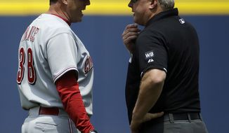 Umpire Bill Miller, right, talks with Cincinnati Reds manager Bryan Price after Miller ejected Price from the game for coming onto the field following an instant replay decision in favor of the Atlanta Braves in the first inning of a baseball game, Sunday, April 27, 2014, in Atlanta. (AP Photo/David Goldman)