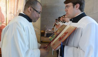Seminarians Brandon Brown, left, and Michael Russo, right, prepares a passage in the Holy Bible during the Mass of Thanksgiving on Sunday, April 27 at the Saint John Paul II National Shrine. Khalid Naji-Allah Special to The Washington Times