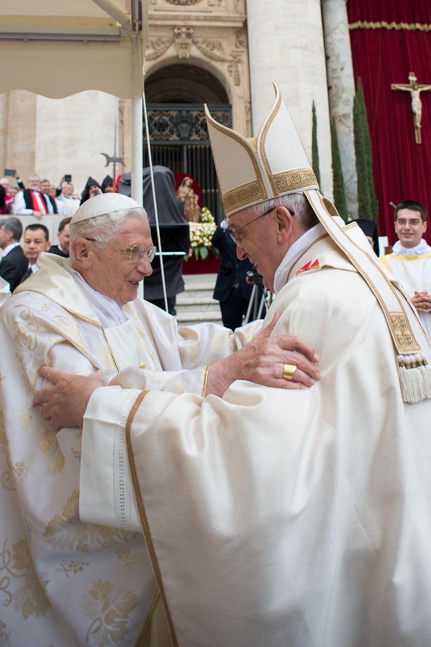 In this photo provided by the Vatican newspaper L'Osservatore Romano, Pope Francis, right, embraces his predecessor Pope Emeritus Benedict XVI, during a ceremony in St. Peter's Square at the Vatican, Sunday, April 27, 2014. Pope Francis has declared his two predecessors John XXIII and John Paul II saints in an unprecedented canonization ceremony made even more historic by the presence of retired Pope Benedict XVI. (AP Photo/L' Osservatore Romano, ho)
